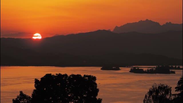 Sonnenaufgang über dem Zürichsee, der Himmel ist rötlich verfärbt.