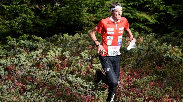 OL-Läufer mit rotem Oberteil rennt durch Büsche am Boden