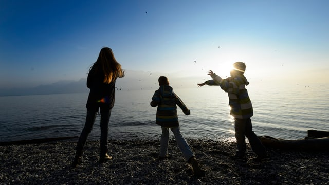 Drei Kinder beim Spielen am See