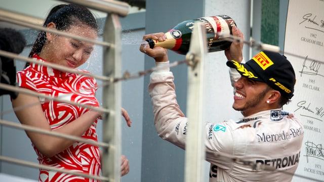 Lewis Hamilton spritzt einer chinesischen Ehrendame Champagner ins Gesicht.