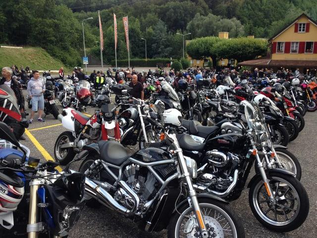 Mehrere Motorräder auf einem Parkplatz.