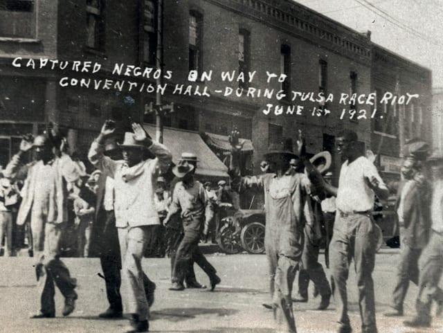 Afroamerikaner laufen mit erhobenen Händen