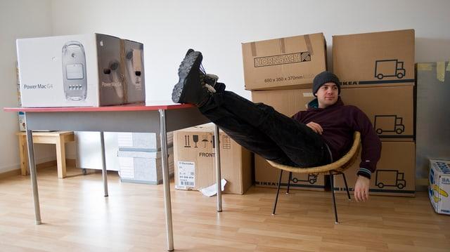 Junger Mann in Wohnung zwischen Umzugskisten