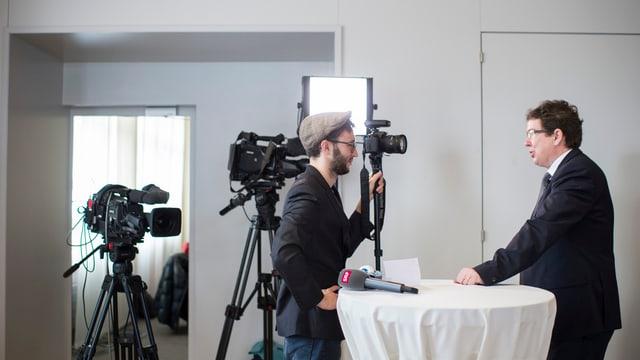 Symbolbild: Rösti steht an einem Tisch, ihm gegenüber ein Mann mit Kamera.