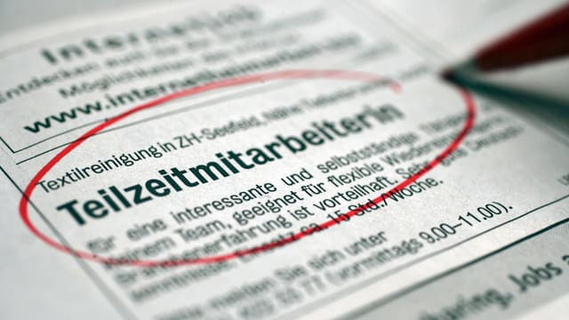 Eine Person auf Stellensuche streicht in einer Zeitung ein Inserat einer Textilreinigung für eine Stelle als Teilzeitmitarbeiterin rot an. (keystone)
