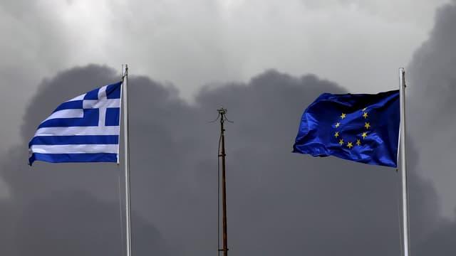 Zwei Fahnen an Masten, die griechische und die EU-Flagge. Himmel mit dunklen Wolken verhangen.