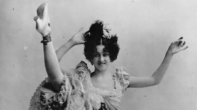 Eine Cancan-Tänzerin hebt ihr Bein hoch.