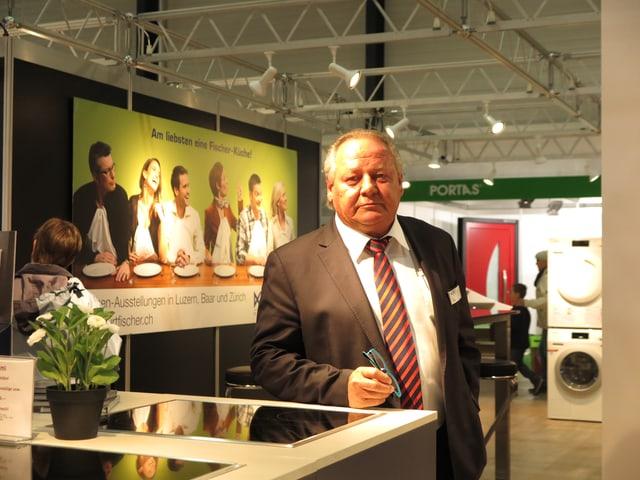 Ein Mann mit kurzen grauen Haaren, rot-schwarzer Krawatte und Anzug steht an eienr Küchenkombination an der Luga.