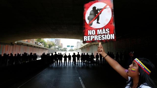 Frau mit einem Plakat gegen Repression, im Hintergrund Polizisten