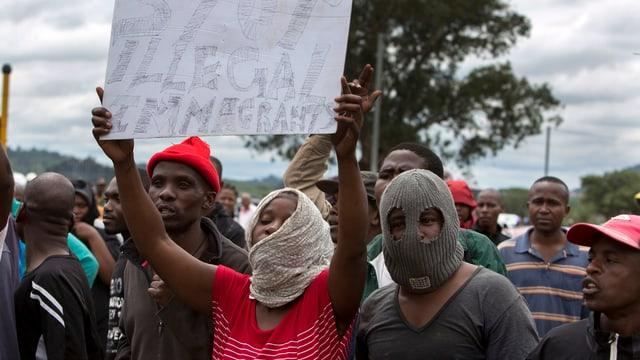 Mehrere Personen, teilweise maskiert, halten ein Plakat hoch.