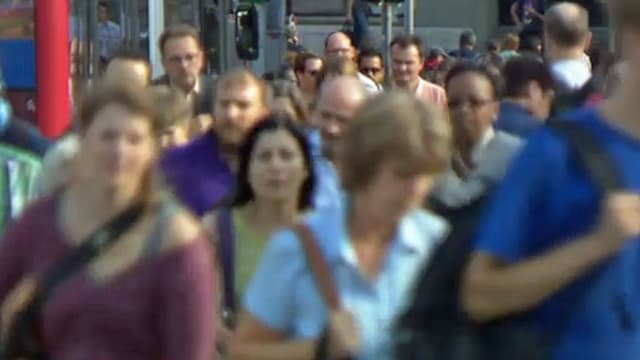 Strassenszene mit vielen vorbeieilenden Menschen.