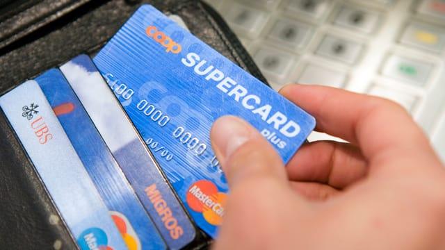Die Supercard von Coop und die Cumulus-Card von Migros in einem Lederportemonnaie.