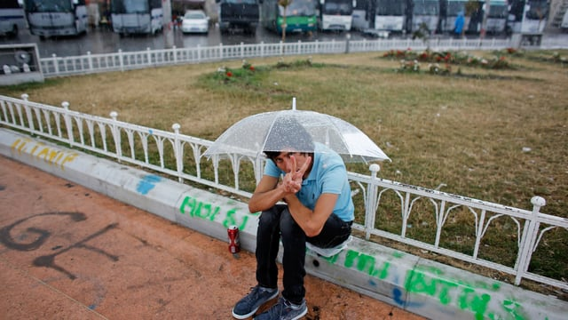 Ein junger Demonstrant unter einem Regenschirm macht mit den Fingern ein Siegeszeichen.