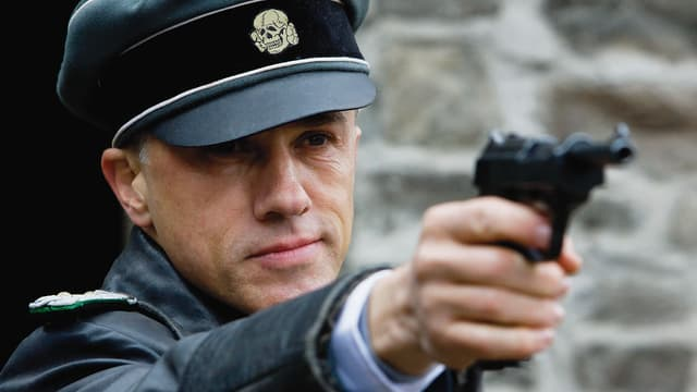 Ein Mann in einer Nazi-Uniform zielt mit seiner Pistole.