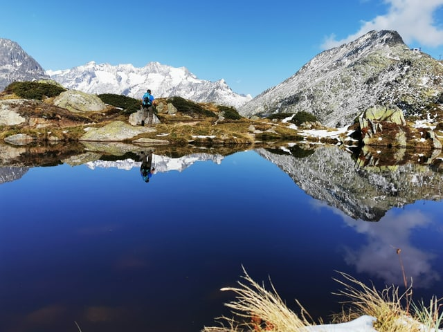 Ein Wanderer an einem Bergsee unter blauem Himmel.