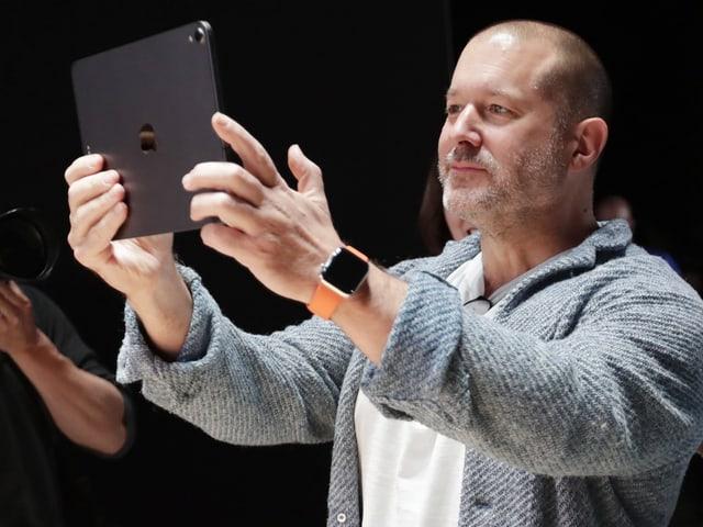 Jony Ive hält sich ein iPad vors Gesicht.