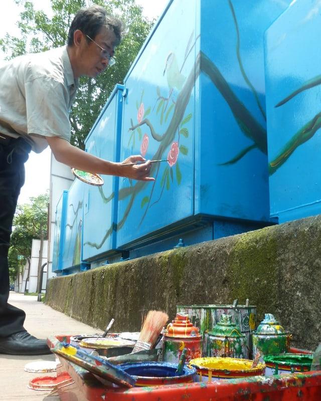 Ein taiwanesischer Maler bei der Arbeit an einem Stromkasten.