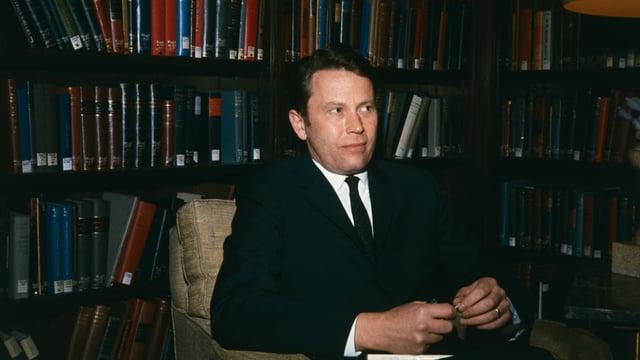 Richard Wilbur sitzt vor einer Bücherwand.