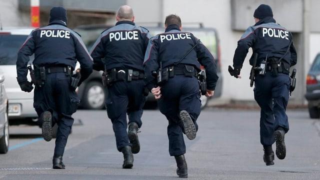 Berner Polizisten rennen durch eine Strasse.