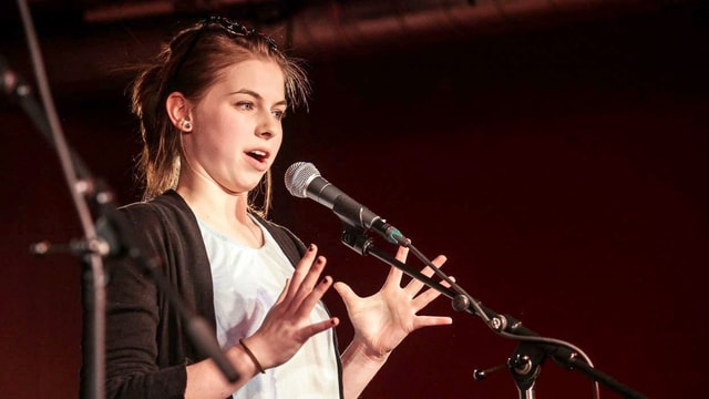 Junge Frau an einem Mikrofon