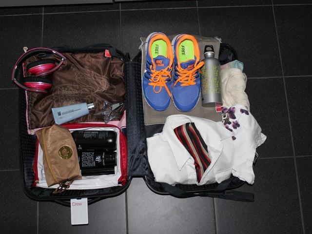 Gepackter Koffer mit Turnschuhen, Kopfhörern.