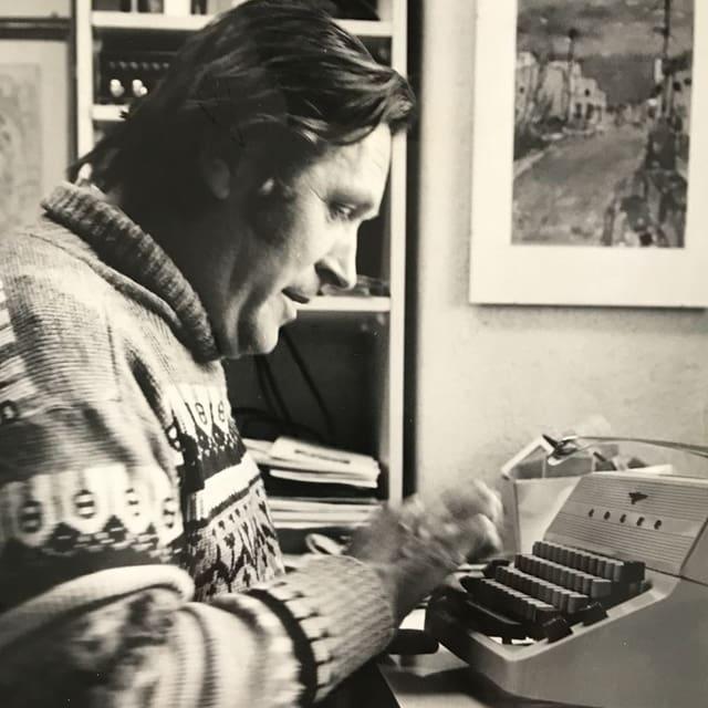 Schwarz-Weiss-Fotografie: Mann in Norweger-Pullover an Schreibmaschine.