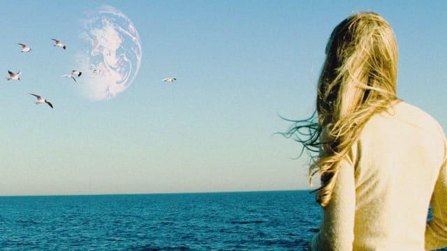 Eine Frau blickt über das Meer. Vögel fliegen über das Meer und es zeichnet sich ein Planet am Firmament ab.