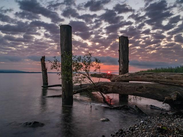 See mit Holzsteg, der ins Wasser ragt. Dämmerung mit Wolken und farbigem Himmel.