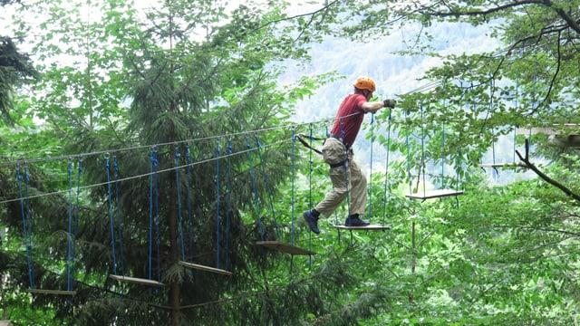 Ein Mann klettert über eine Seilbrücke im Seilpark Gantrisch
