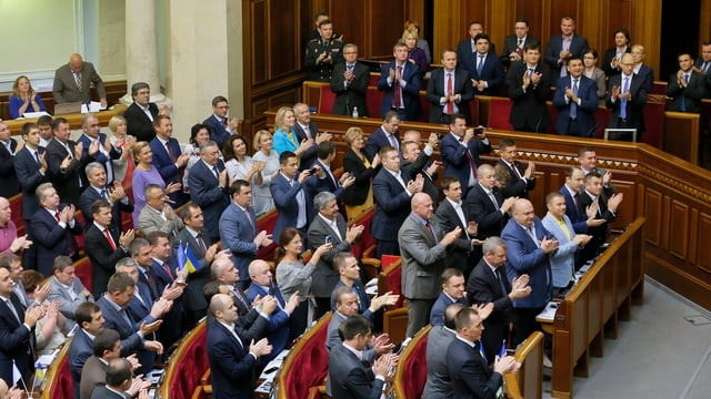 Parlament in Kiew, Abgeordnete stehen und applaudieren.