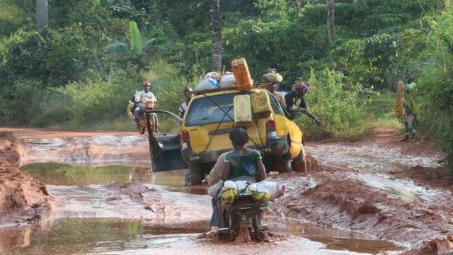 Symbolbild: Strasse im Busch, die von riesigen, metertiefen Pfützen geprägt ist, darauf ein Auto und ein Motorrad.