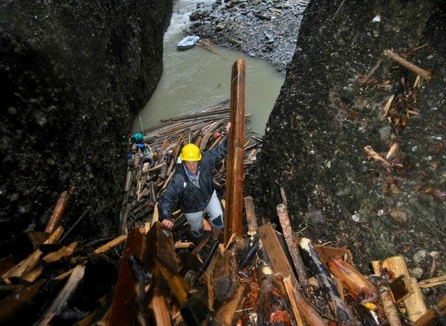 Ein Mann besteigt den Berg aus Schwemmholz.