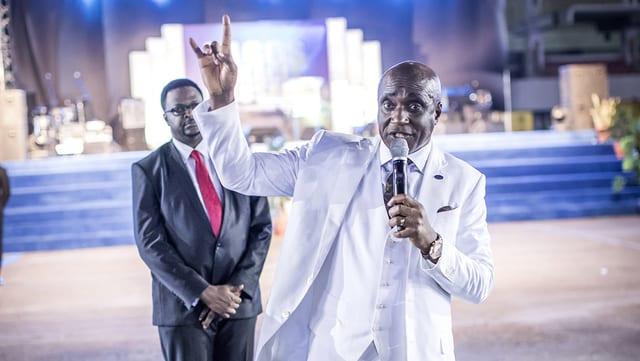 Pastor David Ibiyeomie trägt einen weissen Anzug. Er hält eine Hund an die Luft.