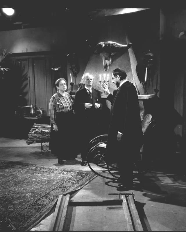 Drei Schauspieler (zwei Männer und eine Frau) im Geisterhaus aus Sicht der Kamera mit Dollyschienen am Boden.
