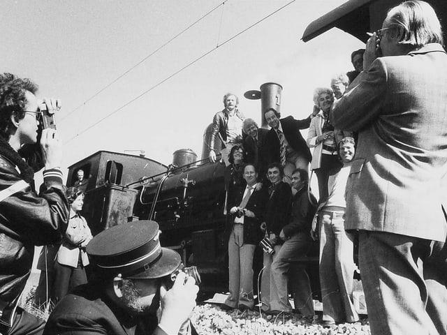 Eine Gruppe von Frauen und Männern vor einer alten Lokomotive.