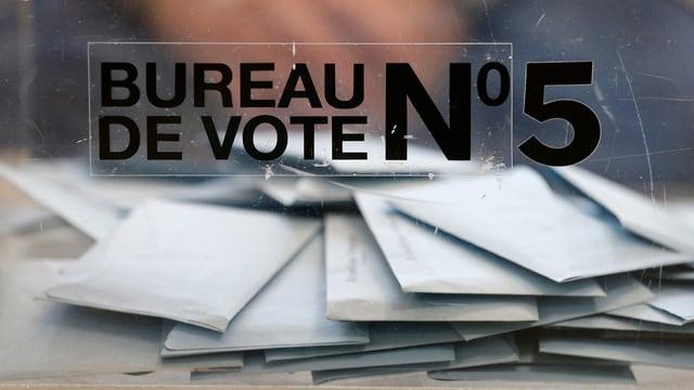 Briefe stapeln sich hinter einer Glasscheibe, auf der «Bureau de Vote No. 5» steht.