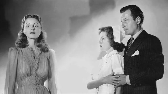 Schwarzweissbild: Ein Mann und eine Frau schauen verängstigt auf eine andere Frau mit ausdruckslosem Gesicht.
