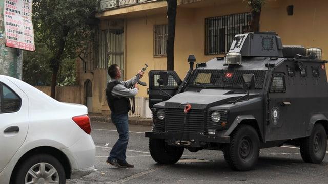 Ein Mann mit Gewehr richtet seine Waffe auf ein Gebäude. Neben ihm ein Panzer.