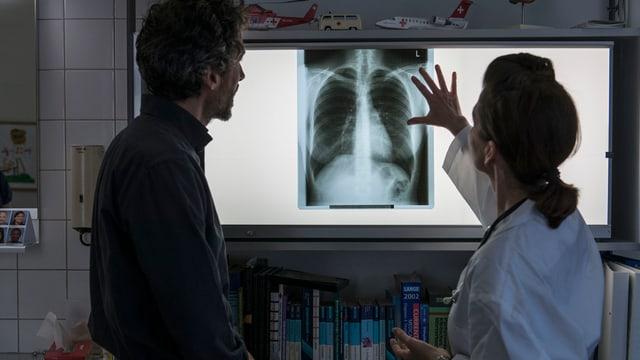 In medi ed ina tgirunza da malsauns stattan davant in maletg da radiografia