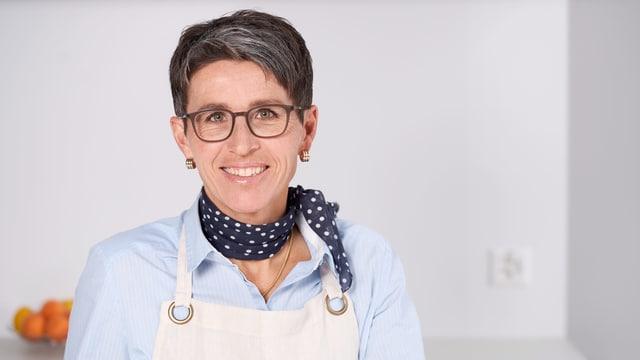 Eine Frau in weisser Kochschürze mit Brille und dunkelblauem Foulard.