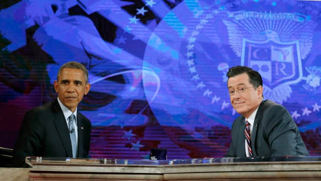 Obama und Gastgeber Colbert sitzen sich vis-à-vis und blicken ins (unsichtbare) Publikum, im Hintergrund das violett-blaue Signet der Sendung.