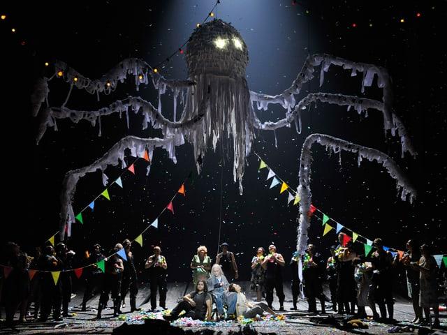 Über der Bühne schwebt ein Ungehäuer (Krake) darunter die Schauspieler.