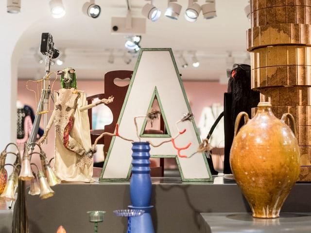 Ein Leuchtbuchstaben A neben einer Vase, Lampe und Skulpturen.