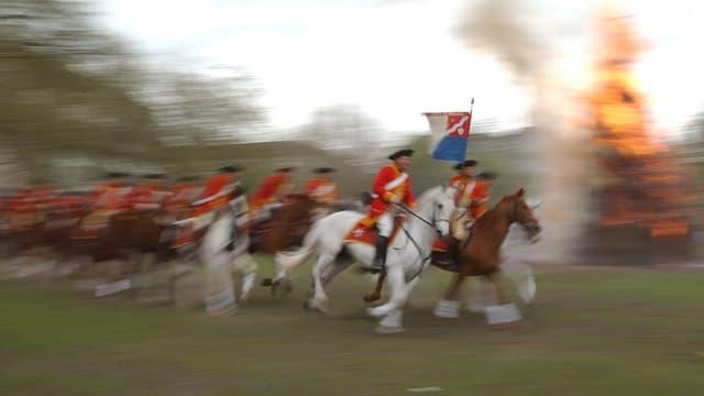 Zünfter reiten mit ihren Pferden um den Böögg