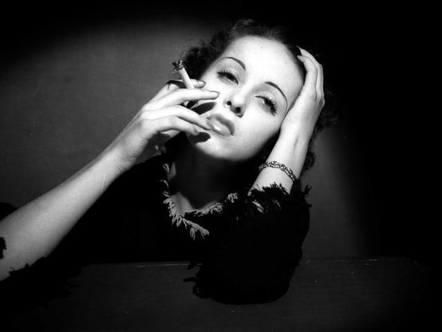 Danielle Darrieux um 1935, rauchend, mit Zigarette in der Hand.