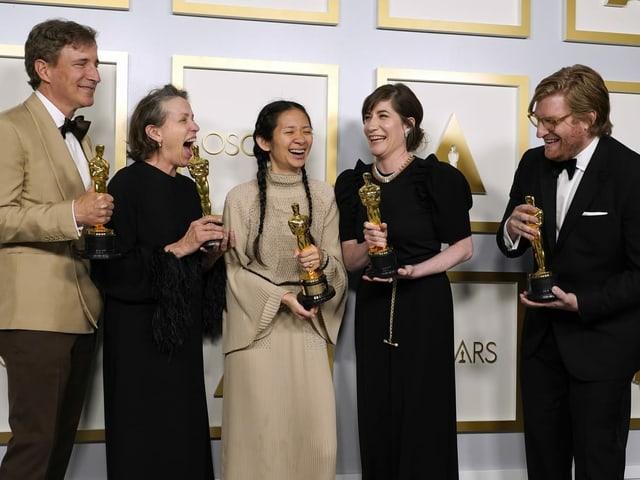 Drei Frauen und zwei Männer mit je einer Oscar-Trophäe in den Händen