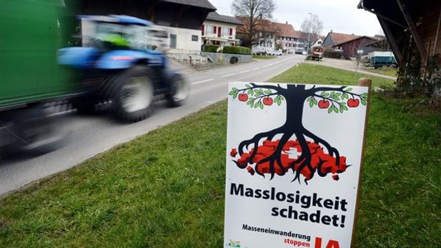 Trakator fährt zu einem Bauernhof, am Boden liegt ein Plakat der SVP zur MEI