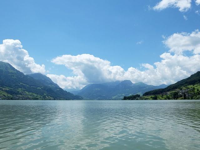 Blick auf den See, im Hintergrund sind die Berge zu sehen.
