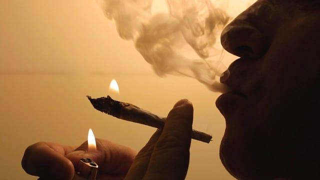 Ein Canabis-Raucher konsumiert einen Joint.