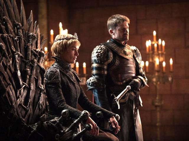 Cersei Lannister auf dem eisernen Thron, neben ihr steht ihr Bruder Jamie.